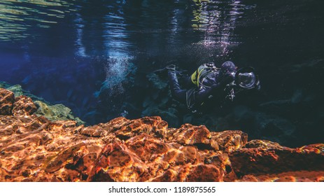 Underwater photography man with a big professional camera diving in a crystal clear cold freezing glacial water in famous fissure Silfra national park Thingvellir Iceland Between two tectonical plates