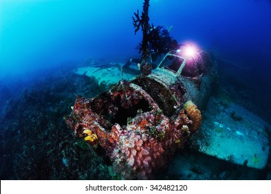 Underwater photography. Photographer diver scuba take a photo of Japanese sea plane, shot down during World War II. Actual under water Photo. 50 meters depth. Japan sea, Far East