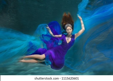 Underwater Queen. Girl mermaid. Underwater scene. A woman, a fashion model in the water in a beautiful dress swims like a fish.
