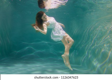 Underwater scene. Girl mermaid with healthy shiny beautiful long hair. A woman, a fashion model in the water in a beautiful dress swims like a fish.