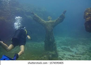 Underwater Sculpture of Jesus with Diver