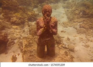 Underwater Sculpture of Praying Child