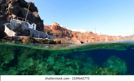 Underwater and sea level photo of iconic islet and church of Agios Nikolaos below iconic village of Oia, Santorini island, Cyclades, Greece