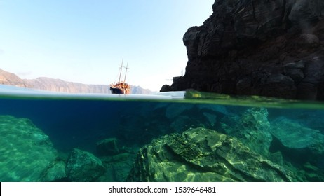 Underwater and sea level photo of iconic islet and church of Agios Nikolaos below village of Oia, Santorini island, Cyclades, Greece