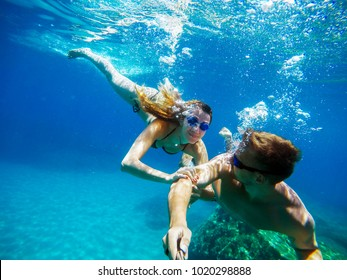 Underwater selfie with a stick of young excited joyful love couple swimming and enjoying with goggles in the exotic turquoise sea at summer vacation or honeymoon.