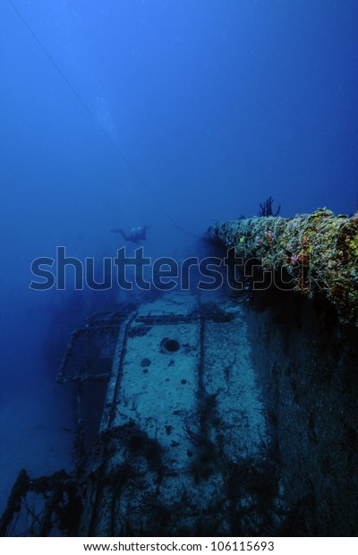 An underwater shipwreck laying on its side in the John Pennekamp State Park in Key Largo, Florida. With a technical diver swimming over it. The USCG Bibb.