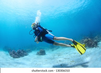 Underwater shoot of a diver swimming in a blue clear water near a bottom