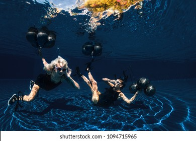 Underwater shoot of flying two women with black balloons