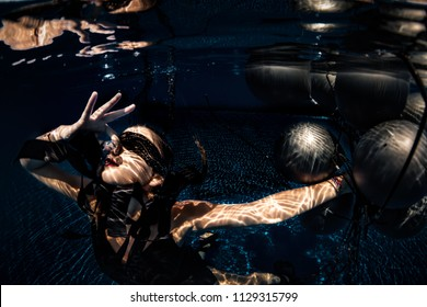 Underwater shoot of flying woman with black balloons