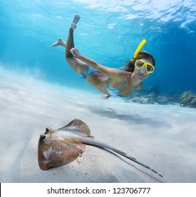 Underwater shoot of a young lady snorkeling and doing skin diving over sandy sea bottom with blue spotted ray on the foreground