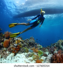 Underwater shoot of a young lady snorkeling and diving on a breath hold over vivid coral reef of tropical island with boat silhouette on surface