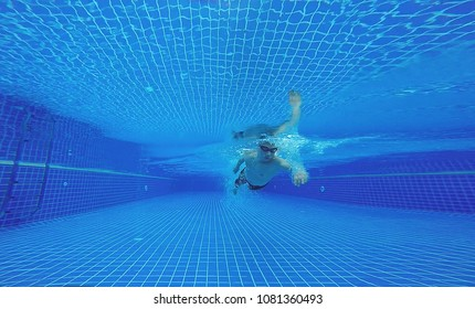 Underwater shot of fit swimmer training in the swimming pool.Amateur male swimmer practicing inside the club house pool.Sport , Health care concept.Copy space for text.