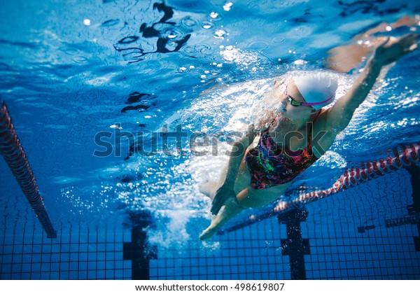 プールで泳ぐのに適した水中撮影。プールの中で泳ぐ女性。