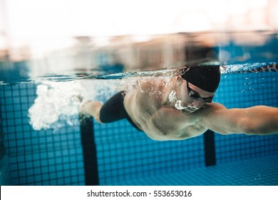 Underwater shot of pro male swimmer in action inside swimming pool. Young sportsman training in the pool.