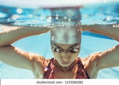 Underwater shot of woman inside swimming pool. Female swimmer in swim cap and goggles inside pool.