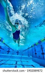 Unterwasseraufnahme einer Frau, die im Pool schwimmt
