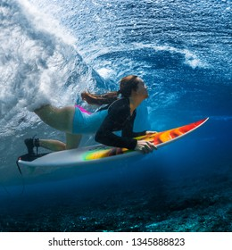 Underwater shot of the young woman surfer diving under the wave with her surfboard