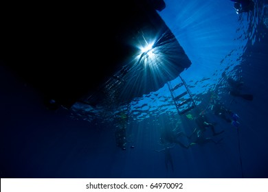 Underwater silhouette view of dive boat  and scuba divers on the surface with rays of sunlight streaming through in Koh Tao, Thailand.