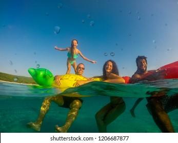 Underwater split screen view of friends on inflatables in sea.