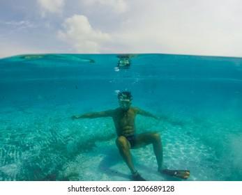 Underwater split screen view of man diving apnea.