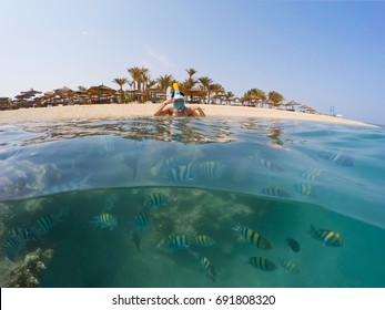 Underwater surface split view in the tropics paradise with fish and coral reef, above waterline view of woman with snorkel mask and paradise beach with parasols. Egypt Marsa Alam vacation concept