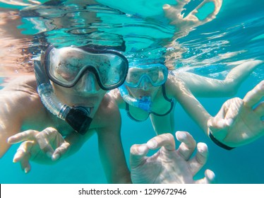 Underwater view of couple snorkeling in the sea and doing ok sign