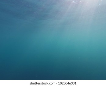 Underwater view with light beams in azure blue sea