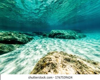 Underwater view of  rocks and white sand in Alghero shore. Sardinia, Italy