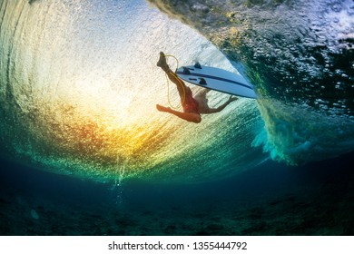 Underwater view of the surfer floating on the water surface after passing the big wave