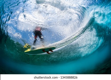 Underwater view of the surfer riding the wave