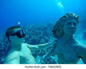 Underwater wide angle selfie of muscular freediver with the mermaid