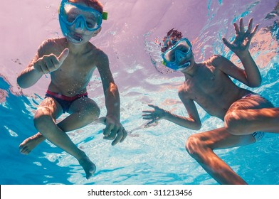 Underwater young brothers kids in swimming pool with mask.