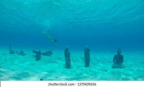 UNDERWATER: Young woman diving and exploring the ruins of old submerged buddha statues sitting on the bottom of the Pacific Ocean near Bora Bora. Tourist girl exploring lost city in French Polynesia.