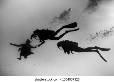 Underwater/scuba diving shot of silhouettes of divers from below, facing up to the surface. High contrast, black and white