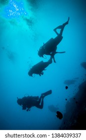 Underwater/scuba diving shot of silhouettes of divers from below, facing up to the surface. High contrast, black and blue image
