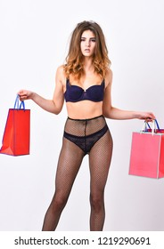 Underwear or lingerie for female. Elite lingerie for sensual girl. Woman tousled hairstyle posing in black lingerie. Girl sexual temptress wear stockings hold shopping bags. Lingerie boutique concept.