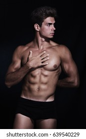 Underwear portrait. A young and attractive man shirtless posing on a black background. Muscular and athletic. Well-defined muscles. Touching the pectoral.