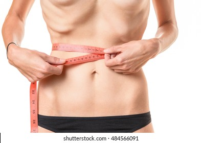Underweight young woman measuring her waist with a tape measure with protruding ribs and hip bones conceptual of anorexia or bulimia, isolated on white