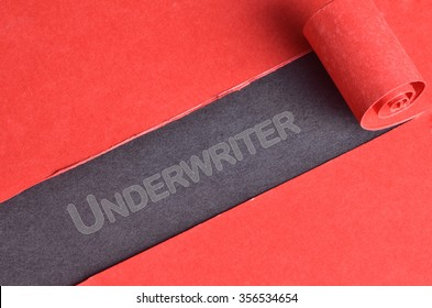 Underwriter word on top of blackboard and torn red paper