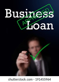 An underwriter writing Business Loan approved on a screen.