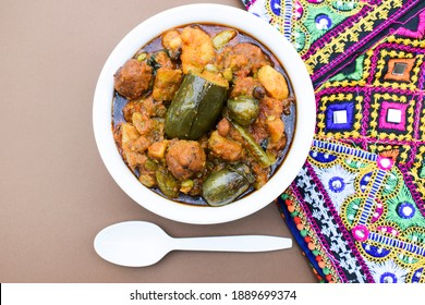 Undhyu or Oondhyu a gujarati delicary dish served in handi bowl with backdrop of gujarati kutchi bharatkam handmade embroidery design. multicolored traditional background. navratri theme food