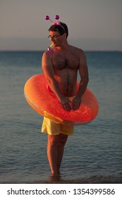 An undressed man at the seashore, equipped by a rubber ring and a rim with glittery horns