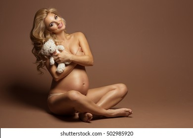 Undressed pregnant woman covering her breast with teddy bear