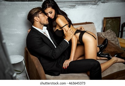 Undressed woman sitting on a couch kissing and touching handsome man
