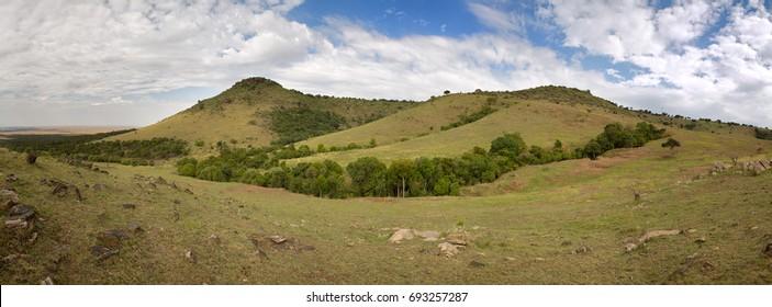 The undulating hills of the Masai Mara, Kenya. Horizontal banner in popular social media proportions.
