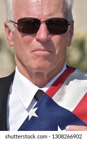 Unemotional Adult Senior Male Politician Wearing Business Suit With Usa Flag