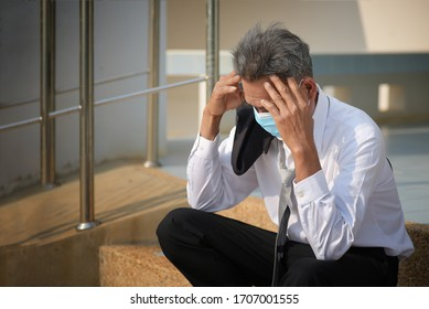 Unemployed Asian man, hopeless businessman sitting hopelessly on the stairs in the central business district due to unemployment due to COVID 19, hopeless grief virus
