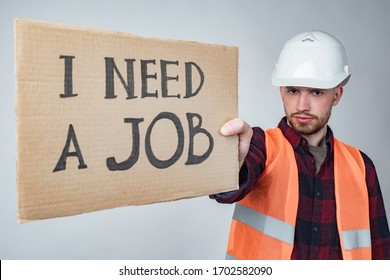 An unemployed Builder with a poster in his hands. The Builder is looking for work. Unemployment in construction.Crisis in the labor market. Dismissal of workers. Termination of the activities of firms