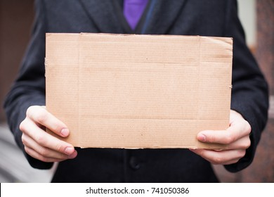 Unemployed businessman in an expensive suit with a blank cardboard sign on the street, close-up. Space for text.
