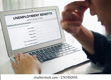 Unemployed depressed person filling out an online unemployment benefits application form using laptop computer.